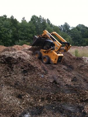 Vinny Bevevino mixes up an acre-wide compost pile to fuel an   urban farm.