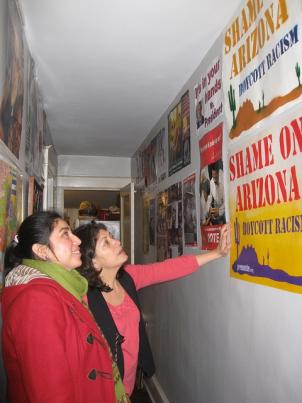 Sonia Umanzor (right) shows posters of immigrant rights and political campaigns that line her hallway at home.